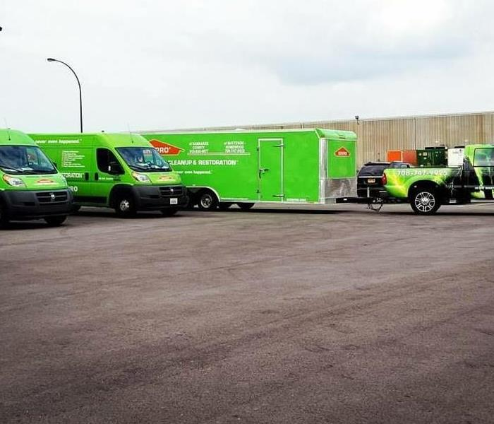 3 bright green trucks pulling out from the warehouse on a bright day