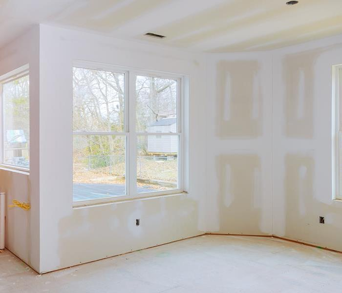 Drywall partially installed in a room with windows.